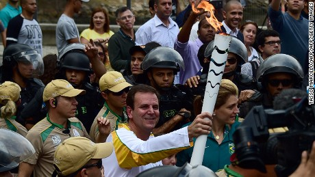 Mayor of Rio Eduardo Paes carries the Olympic torch after its arrival to the Naval Academy on Guanabara Bay.