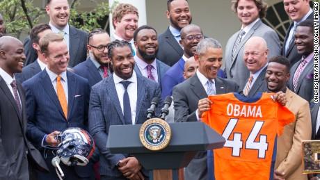 At June celebration   President Barack Obama lifts a Denver Broncos jersey her received in honor of the team's Super Bowl 50 victory over Carolina Panthers.