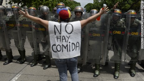 "TOPSHOT - A woman with a sign reading ""There is no food"" protests against new emergency powers decreed this week by President Nicolas Maduro in front of a line of policemen in Caracas on May 18, 2016.  Public outrage was expected to spill onto the streets of Venezuela Wednesday, with planned nationwide protests marking a new low point in Maduro's unpopular rule. / AFP / FEDERICO PARRA        (Photo credit should read FEDERICO PARRA/AFP/Getty Images)"