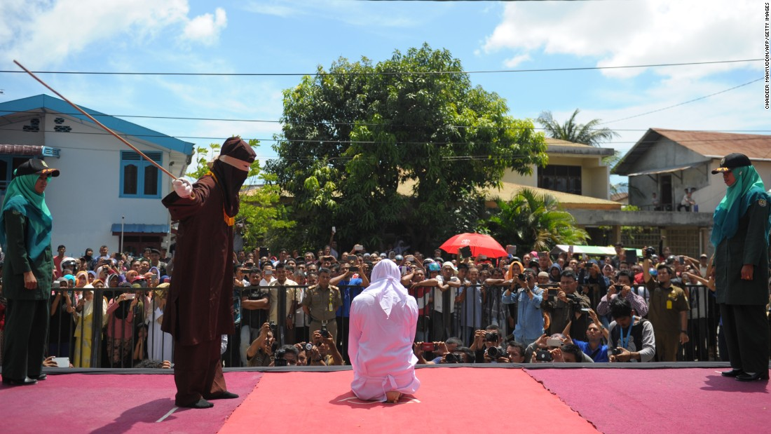 A religious officer in Banda Aceh, Indonesia, canes a young person for dating outside of marriage on Monday, August 1. The Indonesian province of Aceh is strictly Muslim and is the only province in the country implementing Sharia law.
