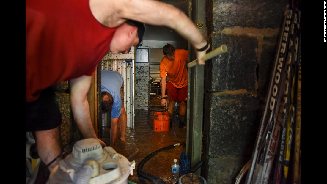 "Pete Price, left, and Al Miller, center, help drain the basement of Dan Durantaye, right, after heavy floods devastated the historic district of Ellicott City, Maryland, on Sunday, July 31. Intense storms unloaded as many as 8 inches of rain in three hours, and the city's Main Street <a href=""http://www.cnn.com/2016/07/31/us/maryland-flooding/"" target=""_blank"">was transformed into a raging river</a> that swept away cars and flooded homes and businesses."