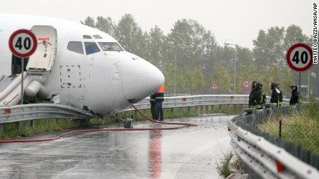 Firefighters work on DHL cargo plane that skidded off a runway overnight at the airport of Bergamo Orio al Serio in northern Italy, crashing through a guard rail onto a highway on Friday, August 5.