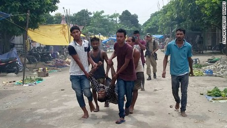 Villagers carry a person injured in an attack Friday on a market in Kokrajhar in India's Assam state.
