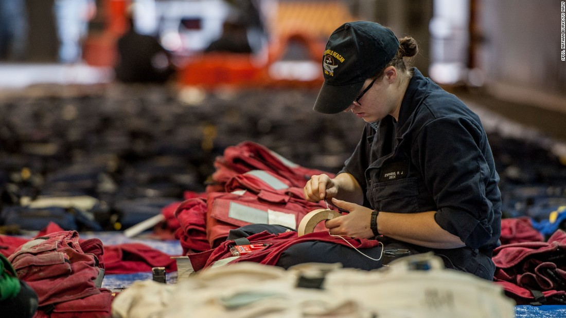 Life preservers. Seaman Rebecca Stephens, from Denver, cuts tape to apply to the batteries of a Firefly distress marker light attached to a life preserver in the hangar bay  USS Ronald Reagan on August 3.