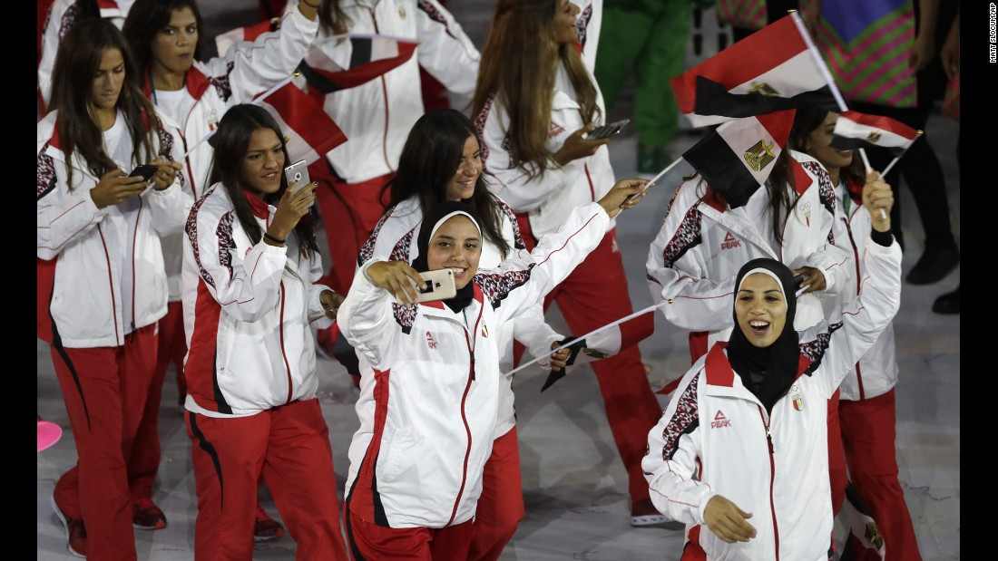 Egyptian athletes take photos as they march into the stadium.