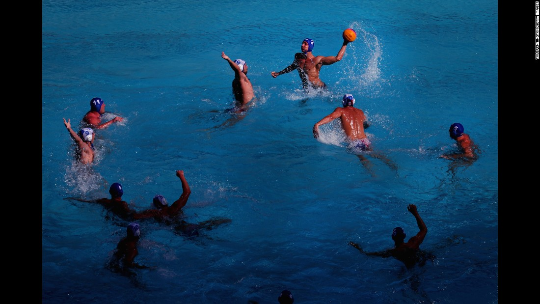 Hungary's Gergo Zalanki, top right, passes the ball against Serbia's Milos Cuk, top left, during the men's water polo preliminary round match between their two countries.