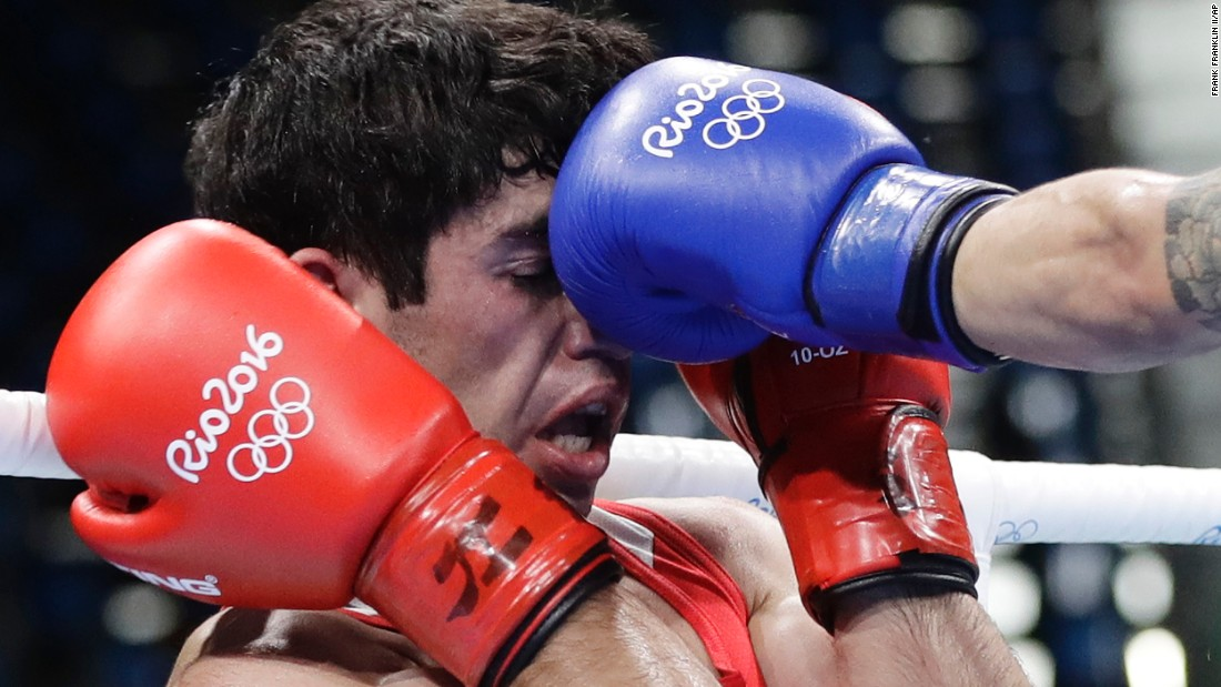 Armenia's Artur Hovhannisyan receives a punch from Spain's Samuel Carmona Heredia during a men's light flyweight 49-kg preliminary boxing match. Hovhannisyan lost the match 0-3.