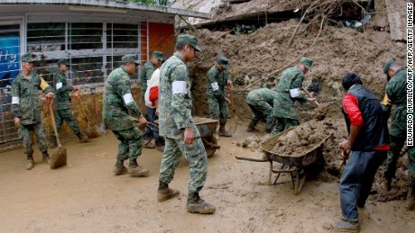 Mexican soldiers help dig out damaged homes in Veracruz, Mexico after they were buried by landslides triggered by Tropical Storm Earl on August 6, 2016.