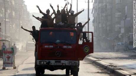 Syrian civil defense volunteers celebrate the breaking of the Aleppo siege.