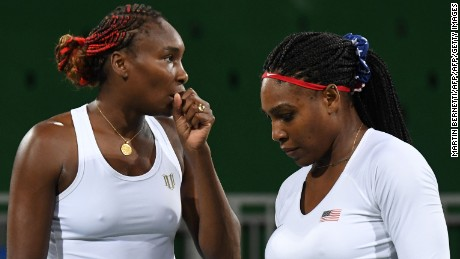 USA's Venus Williams (L) speaks to USA's Serena Williams during their women's first round doubles tennis match against Czech Republic's Lucie Safarova and Czech Republic's Barbora Strycova at the Olympic Tennis Centre of the Rio 2016 Olympic Games in Rio de Janeiro on August 7, 2016. / AFP / Martin BERNETTI        (Photo credit should read MARTIN BERNETTI/AFP/Getty Images)
