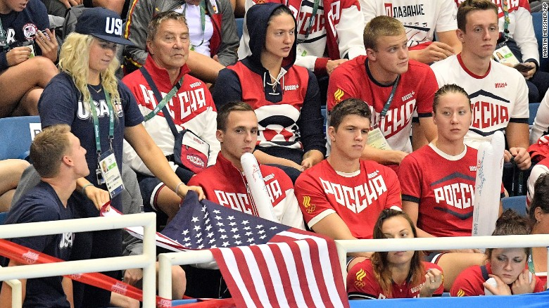 Russia supporters look on as a US team member drapes a US flag during the swimming competitions at the 2016 Summer Olympics, Sunday, Aug. 7, 2016, in Rio de Janeiro, Brazil. (AP Photo/Martin Meissner)
