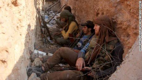 Fighters from Jabhat Fateh al Sham --  formerly the al Nusra Front -- sit in a trench after capturing a key government position in Aleppo.