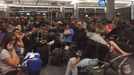 Passengers in the Delta Airlines boarding area at McCarran International Airport in Las Vegas are jammed in to wait as Delta Airlines says all its flights are grounded due to a system outage, Monday, Aug. 8, 2016. Delta Air Lines says it is has grounded flights after experiencing unspecified systems issues. (AP Photo/Bree Fowler)