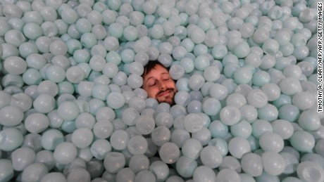 """Jesse Ragan lays in a ball pit at an art installation called """"Anthropodino"""" by Brazilian artist Ernesto Neto on dispay at the Park Avenue Armory in New York May 15, 2009.The dramatic 55,000 square-foot, 80-foot-high piece will be on display until June 14, 2009. AFP PHOTO  TIMOTHY A. CLARY (Photo credit should read TIMOTHY A. CLARY/AFP/Getty Images)"""