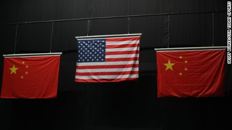 Incorrect Chinese flags are flanked by an American flag during a medal ceremony for the 10m air rifle competition.