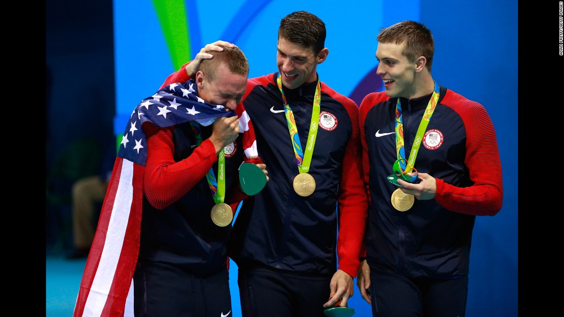 U.S. swimmer Ryan Held cries on the medal stand after winning the 4x100 freestyle relay with Michael Phelps, center, and Caeleb Dressel, right, on Sunday, August 7. Nathan Adrian, not pictured, swam the anchor leg.