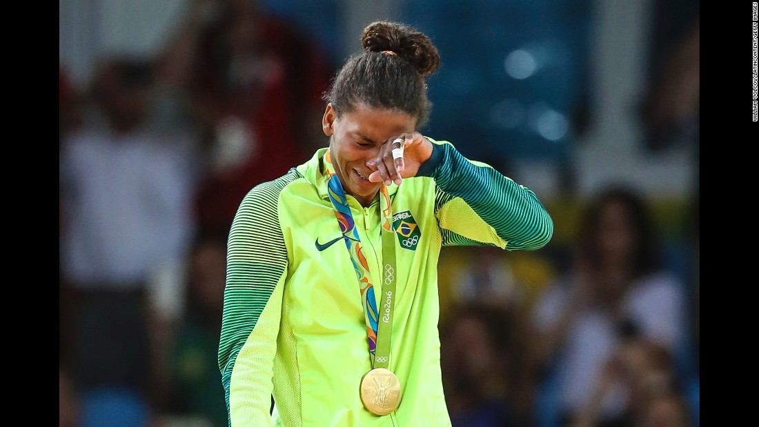 Judoka Rafaela Silva cries on the medal stand after she won Brazil's first gold at the Rio Games. She defeated Dorjsurengiin Sumiyaa in the final of the 57-kilogram weight class.