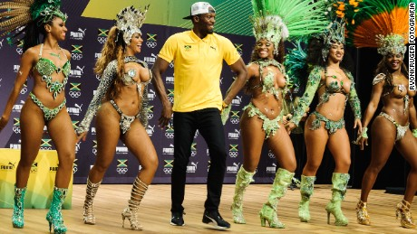 Usain Bolt struts his stuff with samba dancers in Rio.