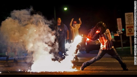 Aug 13, 2014 - St. Louis, Missouri, U.S. - EDWARD CRAWFORD returns a tear gas canister fired by police  who were trying to disperse protesters in Ferguson, Missouri.  Four days earlier, unarmed black teenager Michael Brown was shot to death by a white police officer. The killing ignited riots and unrest in the St. Louis area and across the nation. (Credit Image: ? Robert Cohen/St Louis Post-Dispatch/ZUMAPRESS.com) (Newscom TagID: zumaamericastwelve888956.jpg) [Photo via Newscom]
