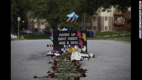 Roses line the street leading to a makeshift memorial for Michael Brown on August 22, 2014 in Ferguson, Missouri.  Crowds continue to gather to march along Florissant Road after Brown was fatally shot by Ferguson Police Officer Darren Wilson on August 9th.