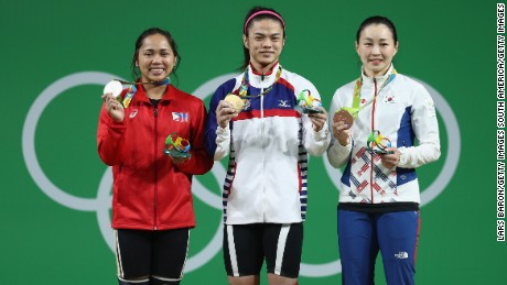 Gold medalist Hsu Shu-ching of Chinese Taipei; silver medalist Hidilyn Diaz of the Philippines; and bronze medalist Jin Hee Yoon of Korea celebrate on the podium after the Women's 53kg Group A weightlifting contest.