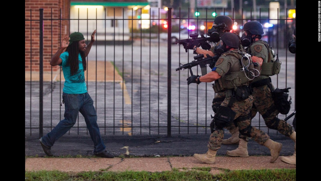 Heavily armed police confronted and eventually detained a man during protests two days after Brown's shooting.