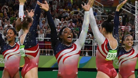 US gymnast Simone Biles (C) and her teammates celebrate after winning the women's team final Artistic Gymnastics at the Olympic Arena during the Rio 2016 Olympic Games in Rio de Janeiro on August 9, 2016. / AFP / Ben STANSALL        (Photo credit should read BEN STANSALL/AFP/Getty Images)