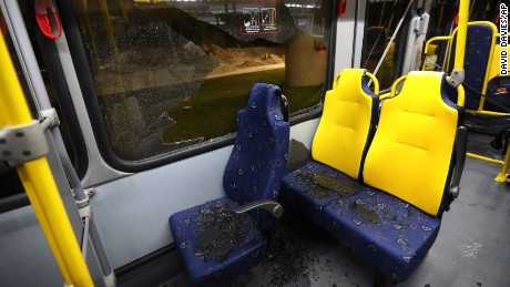 Shattered glass lies on the seats of a media bus in Rio de Janeiro.