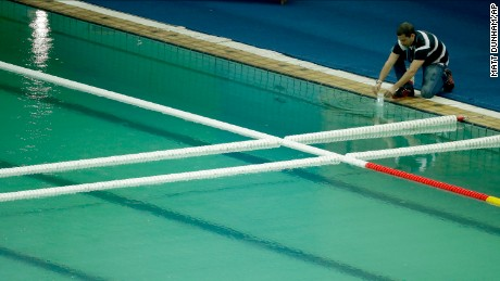 An inspector takes a sample from the water polo pool which turned green on Wednesday.