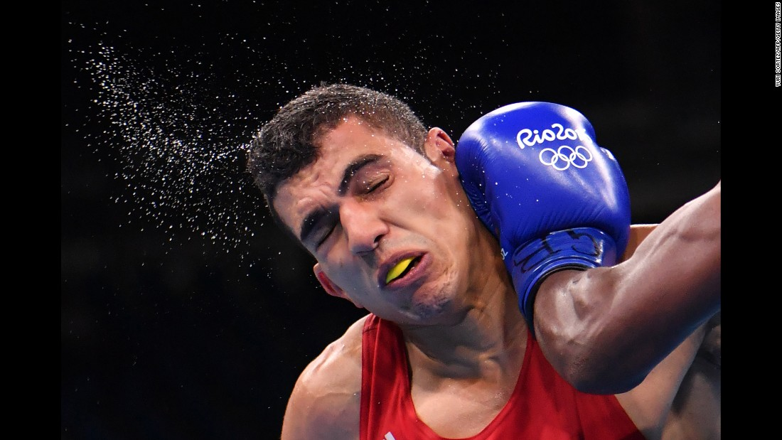 Morocco's Mohammed Rabii is punched by Kenya's Rayton Okwiri during their welterweight bout. Rabii advanced to the quarterfinals.
