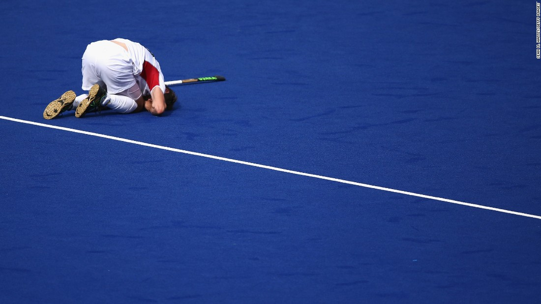 Belgian field hockey player Felix Denayer lies injured on the turf during a match against Spain.