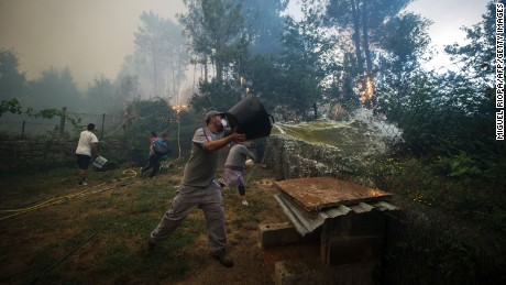 Residents work to fight a wildfire in As Neves in northwestern Spain on Thursday.