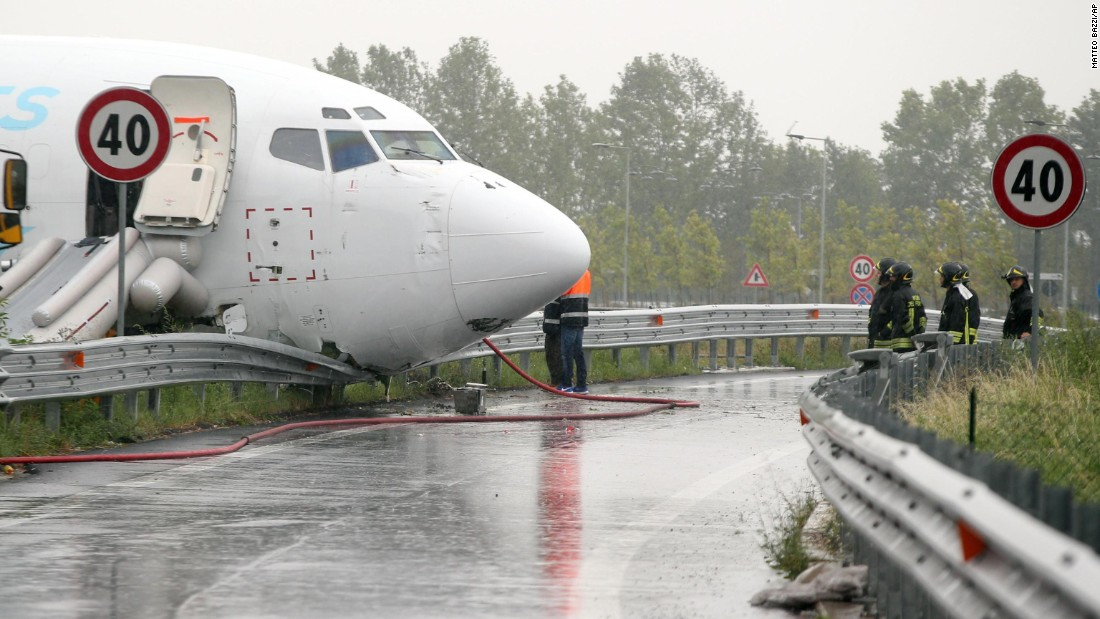 """Firefighters work near a cargo plane that <a href=""""http://www.cnn.com/2016/08/05/europe/italy-plane-overshoots/"""" target=""""_blank"""">skidded off a runway</a> and onto a provincial highway near Bergamo, Italy, on Friday, August 5. No one was hurt."""