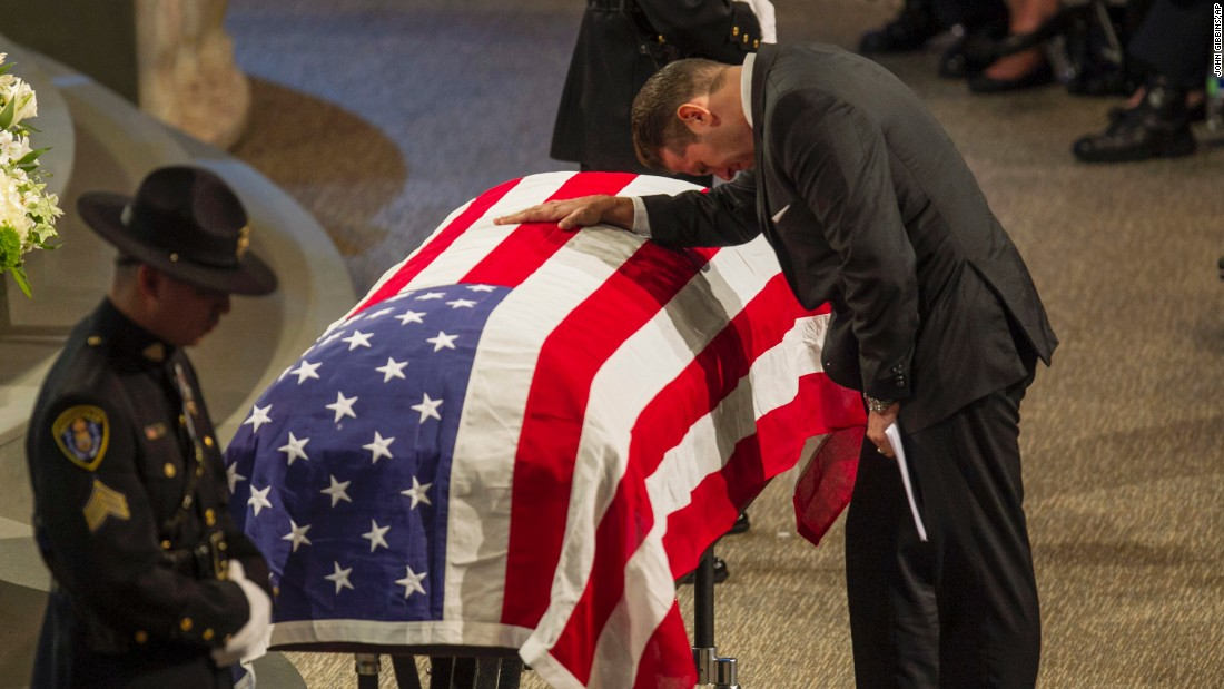 """San Diego Police Sgt. John Iammarino, who worked closely with Jonathan De Guzman, leans on De Guzman's coffin during a memorial service Friday, August 5, in El Cajon, California. De Guzman, 43, <a href=""""http://www.cnn.com/2016/07/29/us/san-diego-police-officers-shot/"""" target=""""_blank"""">was fatally shot last month</a> in the line of duty."""
