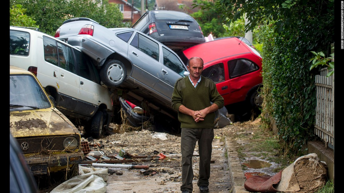 """A man passes damaged vehicles in Stajkovci, Macedonia, after flash flooding on Sunday, August 7. Authorities <a href=""""http://www.cnn.com/2016/08/07/europe/macedonia-storms/"""" target=""""_blank"""">declared a crisis</a> after powerful storms left at least 21 people dead, state-run media said."""
