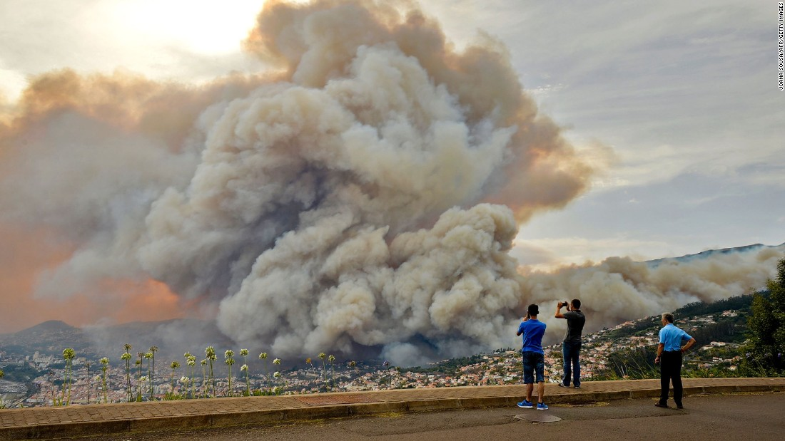 """People take pictures of the smoke rising from <a href=""""http://www.cnn.com/2016/08/11/europe/europe-france-spain-portugal-wildfires/index.html"""" target=""""_blank"""">a wildfire on Portugal's Madeira Island</a> on Tuesday, August 9."""