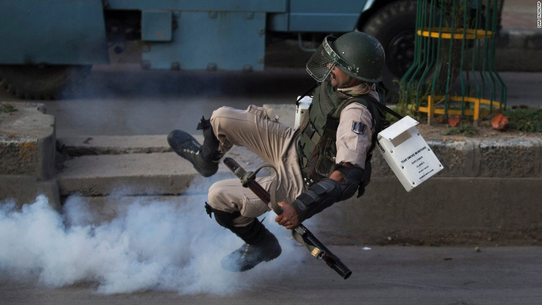 An Indian paramilitary soldier falls down as he tries to kick back an exploded tear gas shell thrown back by Kashmiri Muslim protesters on Monday, August 8.