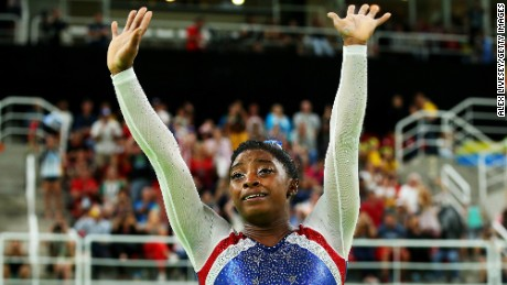 Simone Biles of the United States waves to fans after winning the gold medal during the Women's Individual All Around Final.