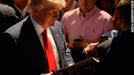 Presumptive Republican presidential nominee Donald Trump admires his portrait on a cover of a magazine during a campaign event at the Duke Energy Center for the Performing Arts  on July 5, 2016 in Raleigh, North Carolina.
