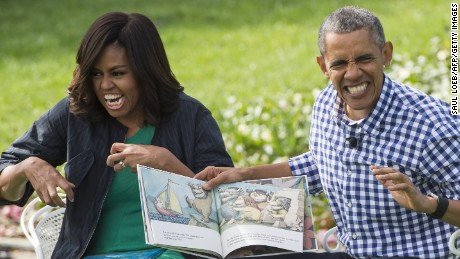"US President Barack Obama and First Lady Michelle Obama read the book, ""Where the Wild Things Are,"" during the annual Easter Egg Roll on the South Lawn of the White House in Washington, DC, March 28, 2016."