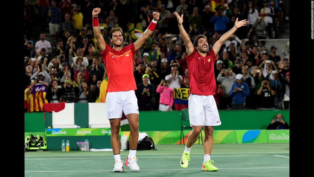 Spanish tennis players Rafael Nadal, left, and Marc Lopez acknowledge the crowd after winning gold in doubles. Nadal won singles gold in 2008.