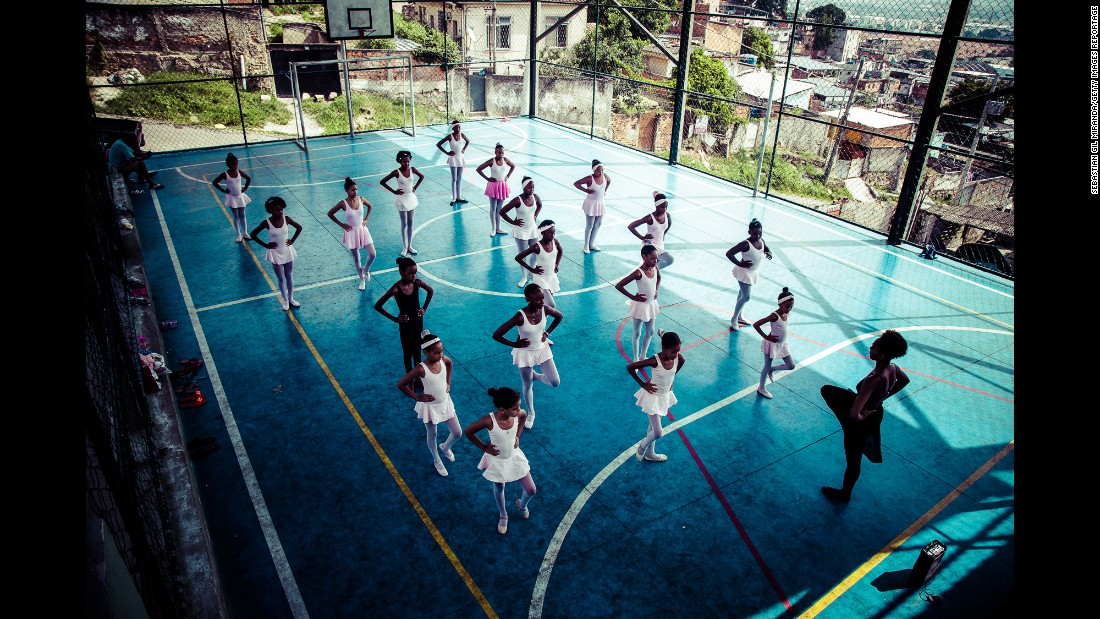 The ballet students practice on a basketball court.