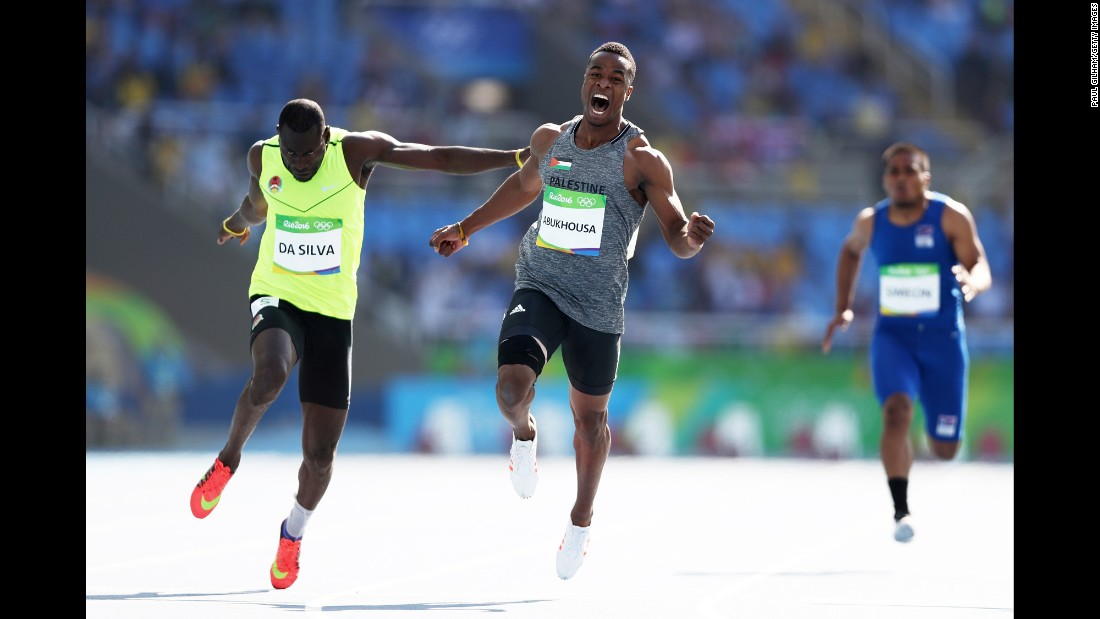 Mohammed Abukhousa of Palestine, center, and Holder da Silva of Guinea-Bissau compete in the men's 100-meter preliminary round. Abukhousa was later carried off the field after an injury.