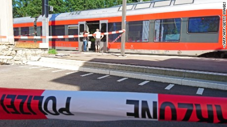 "Policemen stand by a train at the station in Salez, eastern Switzerland, after a man set a fire and stabbed passengers on August 13, 2016. A man set a train carriage in Switzerland on fire using a flammable liquid and stabbed passengers, injuring six people including a six-year-old child, police said. / AFP / newspictures.ch / Beat KAELIN / Switzerland OUT / MANDATORY MENTION OF THE CREDIT ""AFP PHOTO/NEWSPICTURES.CH/BEAT KAELIN""        (Photo credit should read BEAT KAELIN/AFP/Getty Images)"