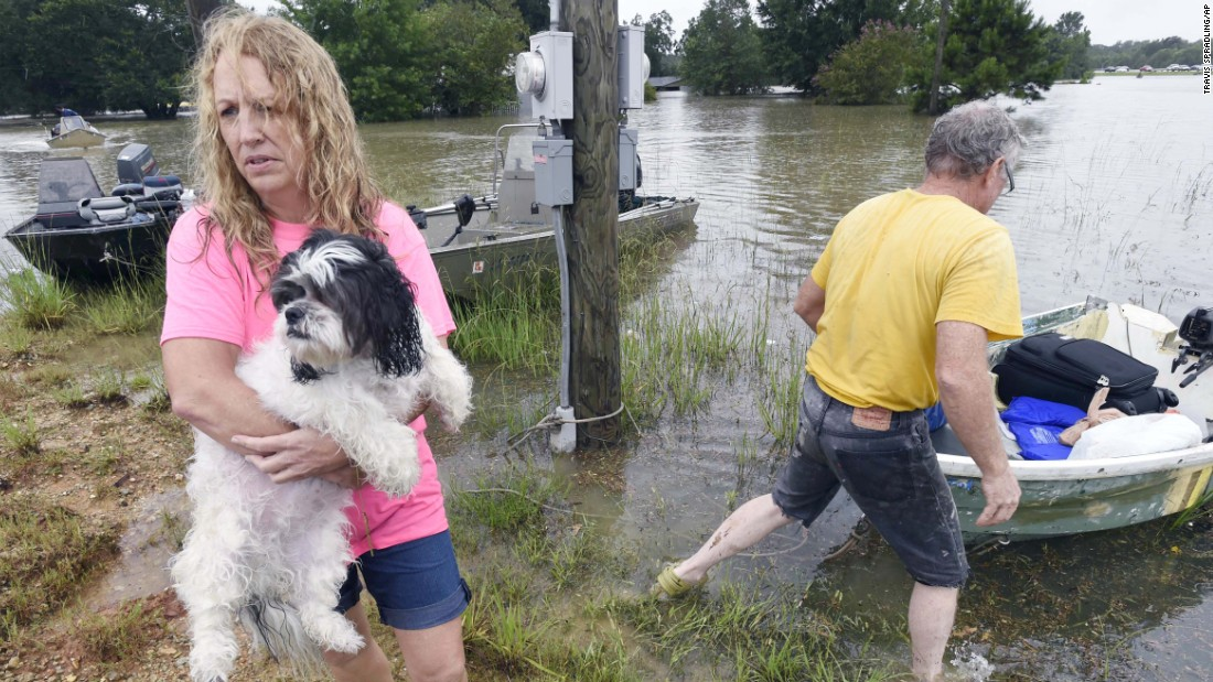 Tammie Wise holds her dog, Mikey, after Jeffrey Lesage helped rescue them in Central, Louisiana, on August 13.