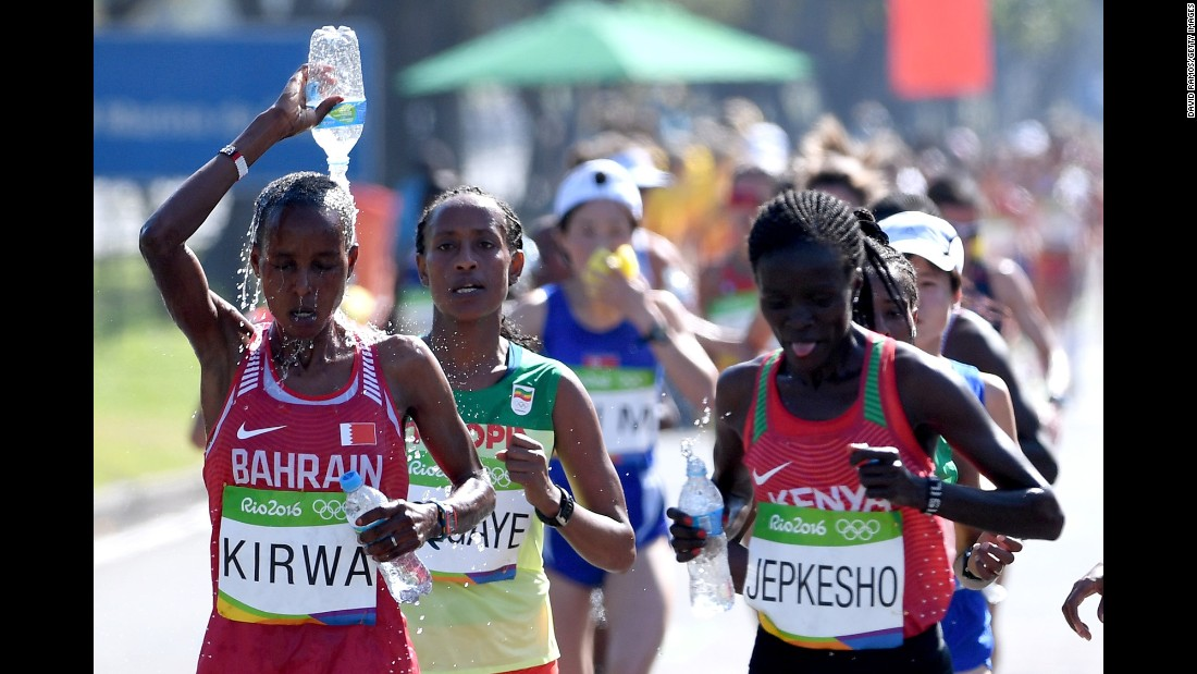 Eunice Jepkirui Kirwa of Bahrain tries to stay cool by pouring water on her head as she runs alongside Visiline Jepkesho of Kenya.