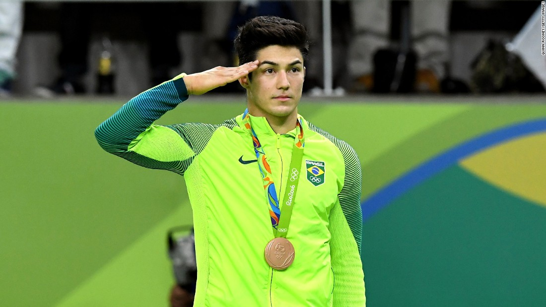 Bronze medalist Arthur Mariano of Brazil salutes during the medal ceremony for Men's Gymnastics Floor Exercise.