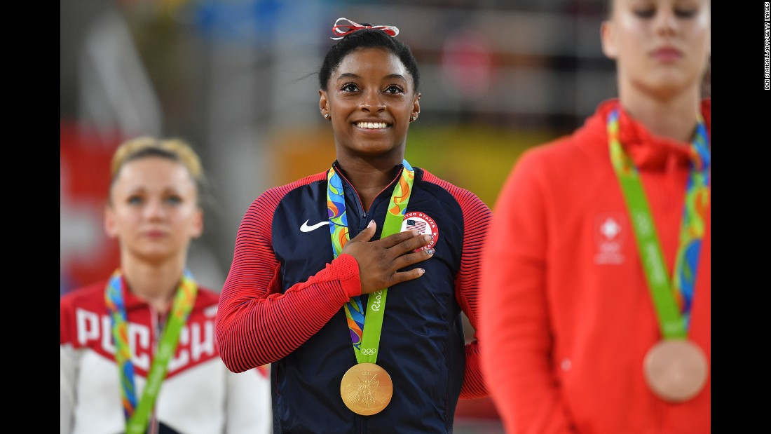 "Simone Biles smiles on the podium after <a href=""http://cnn.com/2016/08/14/sport/simone-biles-third-gold-medal-gymnastics-vault/index.html"" target=""_blank"">winning the gold medal in the women's vault event final.</a>"