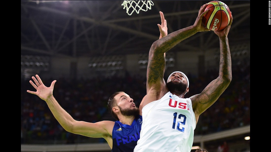 Demarcus Cousins, right, shoots against Joffrey Lauvergne of France during a men's preliminary round Group A basketball game, which the US won 100-97.