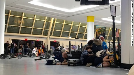 Passengers get down at the immigration control while police looking for an active shooter at JFK International airport in New York on August 14, 2016. Unconfirmed reports of shots fired at New York's main airport triggered scenes of panic, massive evacuations and huge delays late Sunday. There was no immediate confirmation of injuries or arrests, but Port Authority police evacuated at least two terminals at John F. Kennedy International Airport out of precaution.  / AFP PHOTO / Brigitte DUSSEAUBRIGITTE DUSSEAU/AFP/Getty Images